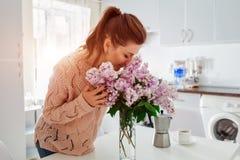 L'allergia libera Lillà odorante della donna felice in cucina moderna Concetto stagionale di allergia Fotografie Stock