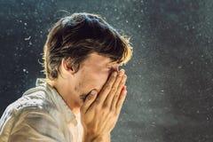 L'allergie pour épousseter des éternuements d'un homme parce qu'il est allergique pour épousseter la poussière vole dans le ciel  photographie stock libre de droits