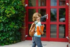 L'allievo allegro ha guardato indietro vicino ad una porta della scuola Fotografia Stock Libera da Diritti
