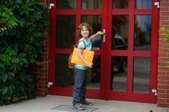 L'allievo apre una porta della scuola Fotografia Stock Libera da Diritti