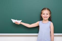 L'allievo con gli origami spedisce la posa al consiglio scolastico, spazio vuoto, concetto di istruzione Fotografia Stock Libera da Diritti