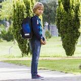 L'allievo con lo zaino pronto va a scuola esterno Fotografia Stock