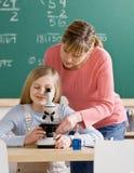 L'allievo d'aiuto dell'insegnante registra il microscopio Immagine Stock Libera da Diritti