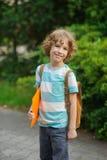 L'allievo del supporto della scuola elementare su un cortile della scuola e sui sorrisi Fotografia Stock Libera da Diritti