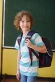 L'allievo della scuola elementare sta nella classe vicino ad un bordo Fotografie Stock