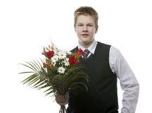 L'allievo delle classi senior in un uniforme scolastico con un mazzo dei fiori Immagine Stock