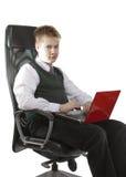 L'allievo di alte classi in un uniforme scolastico con un taccuino si siede in un sedile di lavoro Fotografia Stock Libera da Diritti