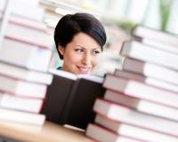 L'allievo femminile è circondato con i libri Fotografia Stock