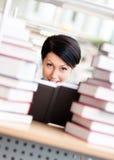 L'allievo femminile è circondato con i mucchi dei libri Fotografia Stock