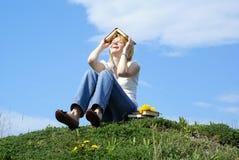 L'allievo femminile esterno sopra gren l'erba con i libri Fotografie Stock Libere da Diritti