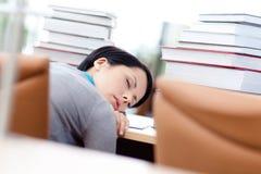 L'allievo femminile faticoso dorme allo scrittorio Fotografie Stock