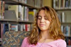 L'allievo femminile grazioso ascolta musica in libreria Fotografia Stock Libera da Diritti
