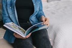 L'allievo femminile legge il libro alla libreria Conoscenza La ragazza sta leggendo uno scomparto giornale Tiene un giornale Immagine Stock Libera da Diritti