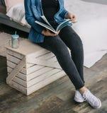 L'allievo femminile legge il libro alla libreria Conoscenza La ragazza sta leggendo uno scomparto giornale Tiene un giornale Fotografia Stock Libera da Diritti