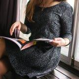 L'allievo femminile legge il libro alla libreria Conoscenza La ragazza sta leggendo uno scomparto giornale Tiene un giornale Fotografia Stock