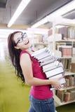 L'allievo femminile trasporta i libri alla libreria Fotografia Stock