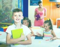 L'allievo sorridente del ragazzo che sta nella scuola elementare classifica Fotografia Stock