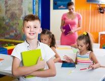 L'allievo sorridente del ragazzo che sta nella scuola elementare classifica Immagini Stock Libere da Diritti