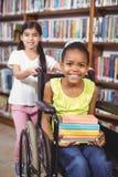 L'allievo sorridente nella tenuta della sedia a rotelle prenota nella biblioteca Fotografie Stock Libere da Diritti