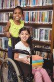 L'allievo sorridente nella tenuta della sedia a rotelle prenota nella biblioteca Fotografie Stock