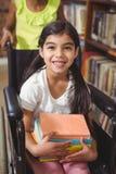 L'allievo sorridente nella tenuta della sedia a rotelle prenota nella biblioteca Immagine Stock