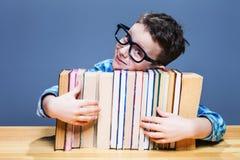 L'allievo in vetri abbraccia i libri, concetto di istruzione Immagini Stock Libere da Diritti