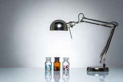 L'allumage vers le haut de la bouteille dope la médecine de pilule avec la lampe de bureau Photo stock