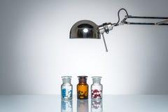 L'allumage vers le haut de la bouteille dope la médecine de pilule avec la lampe de bureau Photo libre de droits