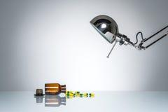 L'allumage vers le haut de la bouteille dope la médecine de pilule avec la lampe de bureau Photos libres de droits
