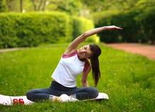 L'allungamento allegro della giovane donna, facente la forma fisica si esercita in parco Fotografie Stock