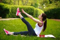 L'allungamento allegro della giovane donna, facente la forma fisica si esercita in parco Immagini Stock
