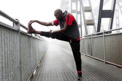 L'allungamento americano nero del corridore muscles prima della corsa Immagine Stock Libera da Diritti