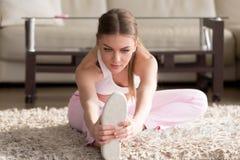 L'allungamento della giovane donna, scaldantesi, risolve gli esercizi a casa Fotografie Stock Libere da Diritti