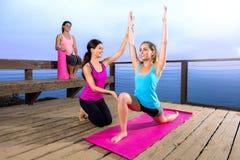 L'allungamento di esercizio dello studente del principiante di aiuti del guru dell'istruttore dell'insegnante di yoga posa all'ap Fotografie Stock Libere da Diritti