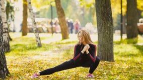 L'allungamento di modello di bikini-forma fisica bionda femminile attraente sexy nel parco di autunno su terra ha coperto le fogl Fotografie Stock Libere da Diritti