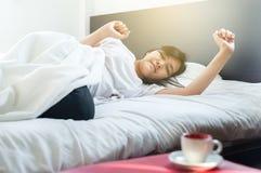 L'allungamento e lo sbadiglio asiatici della femmina sul letto dopo svegliano di mattina Fotografia Stock