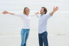 L'allungamento felice delle coppie distribuisce alla spiaggia Fotografie Stock Libere da Diritti
