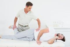 L'allungamento maschio del fisioterapista equipaggia la gamba Fotografia Stock Libera da Diritti