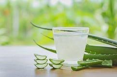 l'aloe fresco vera lascia e succo di vera dell'aloe in vetro sulle sedere di legno Immagini Stock