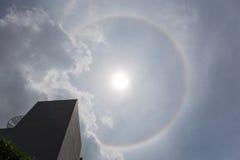 L'alone intorno al sole con l'orizzonte della costruzione e del cielo nuvoloso, Na Immagini Stock
