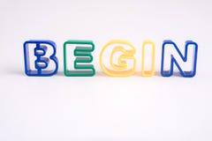 L'alphabet en plastique sur le fond blanc avec le mot commencent Images libres de droits
