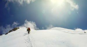 L'alpinista arriva alla sommità di un picco nevoso Fotografie Stock