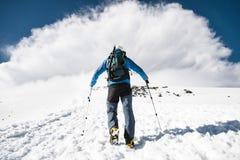 L'alpinista aumenta in salita per incontrare una tempesta della montagna che viene dalla montagna Fotografie Stock Libere da Diritti