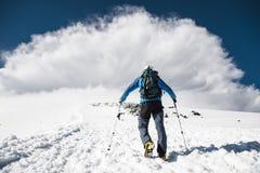 L'alpinista aumenta in salita per incontrare una tempesta della montagna che viene dalla montagna Fotografie Stock
