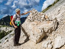 L'alpinista che dispone una pietra su un mucchio di pietra immagini stock