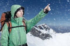 L'alpinista che indica al picco, stante contro un paesaggio della montagna di inverno Immagini Stock Libere da Diritti