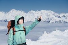L'alpinista che indica al picco, stante contro un paesaggio della montagna di inverno Fotografia Stock