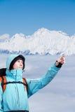 L'alpinista che indica al picco, stante contro un paesaggio della montagna di inverno Immagini Stock