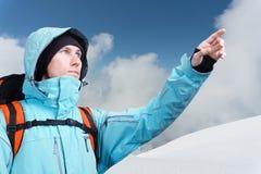 L'alpinista che indica al picco, stante contro un paesaggio della montagna di inverno Fotografia Stock Libera da Diritti
