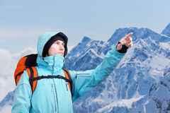 L'alpinista che indica al picco, stante contro un paesaggio della montagna di inverno Immagine Stock